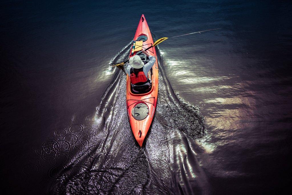 Woman paddling her kayak on a lake